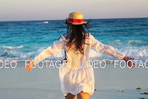 Back view of beautiful woman on tropical seashore in sunset enjoying the sea view. Happy girl in dress in slow motion