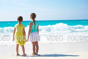 Adorable little kids play together on the beach at shallow water