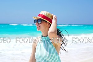 Beautiful woman on summer holidays smiling happy on white beach. Happy girl walking in summer dress. SLOW MOTION