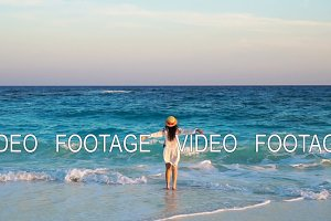 Back view of beautiful woman in hat on summer holidays on white beach. Happy girl enjoy the sea view in slow motion