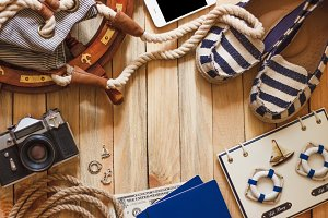 Striped slippers, camera, phone and maritime decorations, wooden background