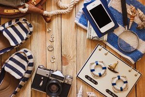 Striped slippers, camera, phone and maritime decorations, top view