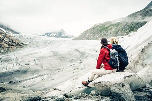 Young Couple Hiking In The Swiss Alps, Taking A Break