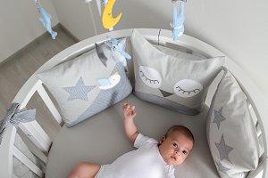 newborn lies in the round white bed