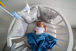 newborn lies in the round white bed with mobile