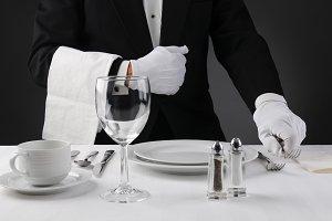 Waiter Setting Formal Dinner Table