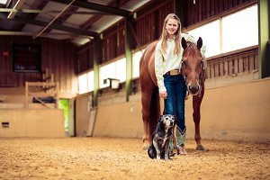 Young Cowgirl With Her Horse And Dog