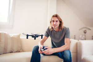 Young Man Playing With A Small Quadrocopter Drone
