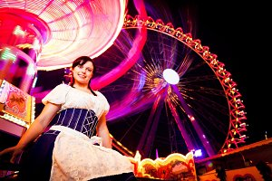 Young Woman Standing Next To Brightly Colored Carousel