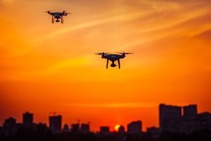 Two modern Remote Control Air Drones Fly with action cameras in dramatic orange sunset sk