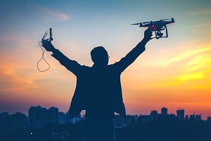 Silhouette of man holding switched on Drone