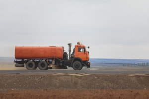 A red watering truck at highway among field - construction work