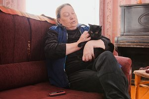 Grand,other - old lady at home - senior woman sits on sofa with black cat