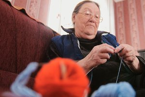 Woman pensioner home - lady knits wool socks sitting on the sofa - hobby