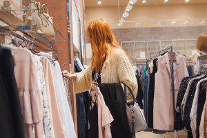 Sale - woman in dress store chooses a clothes - shopping concept