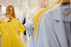 Adorable woman in a clothing store chooses a yellow dress - shopping concept