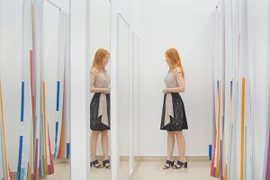Girl in clothing store chooses dress near mirror in fitting room - shopping concept