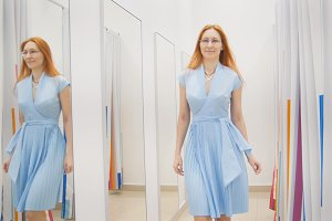 Young woman chooses blue dress near mirror in fitting room at store