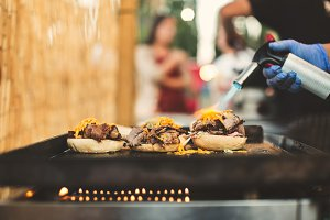 Person using gas torch for cooking burgers