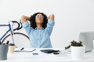 Beautiful young businesswoman with curly hair leaning back in chair, keeping hands behind her head and closing eyes while having a small break, doing paperwork at her workplace. People and business