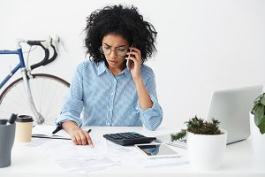 Frustrated female secretary with Afro hairstyle feeling stressed while answering phone call on her first day in office. Serious businesswoman talking on mobile, working through finances at workplace