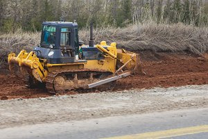 Equipment for road construction - yellow excavator on a construction site
