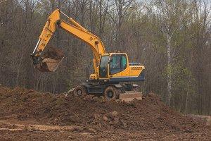 Orange excavator at work - road construction for new highway