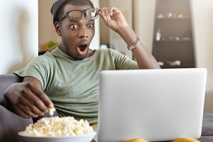 Stunned young Afro American male taking his glasses off and opening mouth widely in astonishment while watching detective series online on laptop on sofa at home, having popcorn, feeling excited