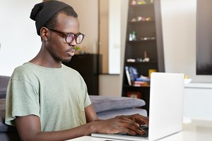 Dark-skinned stylish freelancer sitting at his workplace at home keyboarding on notebook computer. Young African male blogger in eyewear typing new article on blog using laptop pc indoors