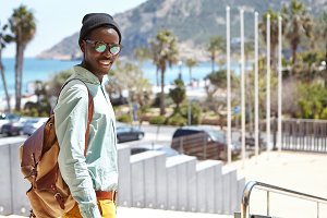 Trendly looking African student in hat and shades enjoying sunny warm weather, walking to urban beach to meet friends after college. Black tourist exploring beauties and attractions of foreign city