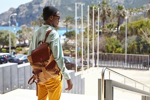Rear view of stylish Afro American man with knapsack standing in urban setting with mountains and azure sea in background, waiting for girlfriend to have a walk on sunny day. People and lifestyle