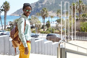 Fashionable attractive young black European backpacker dressed stylishly having walk outdoors at daytime, spending summer holidays in resort town. People, vacations, lifestyle, travel and tourism