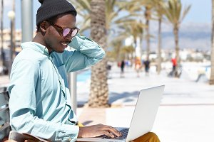 Fashionable young Afro American freelancer wearing stylish clothes and accessories sitting on bench, using laptop pc for remote work, feeling tired, going to have a rest and walk along sea shore