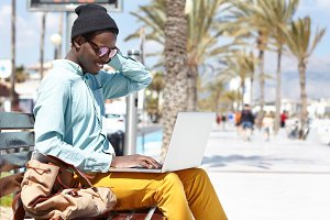 Cheerful dark-skinned male using laptop outdoors, sitting on bench along promenade on city beach, enjoying online communication, having video call with his girlfriend during vacations abroad