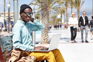 People, modern technology and communication concept. Good looking young African man spending great time outdoors, enjoying sunny day by the ocean, sitting with laptop on bench along promenade