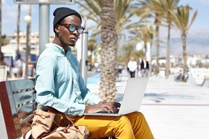 In search of inspiration. Concentrated handsome young African American male freelance worker using notebook computer for remote work, having thoughtful look, sitting on bench in urban surroundings