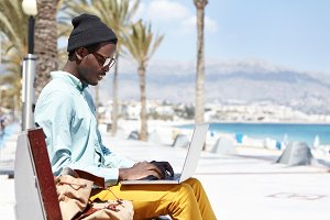 Modern technology, people, lifestyle and communication. Stylish young dark-skinned writer in hat and shades typing on keyborad on generic laptop while working on new book outdoors by the ocean