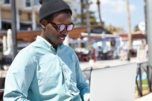 Outdoor portrait of relaxed young black male in stylish headwear and sunglasses using notebook computer, enjoying online communication with friend via video call, sitting on bench in urban setting