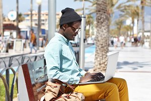 Happy young Afro American blogger wearing trendy clothing sitting on bench on urban beach, using laptop pc for while working distantly on new article for online magazine, looking cheerful and inspired