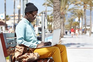 Handsome fashionable African American male freelancer dressed stylishly keyboarding via laptop computer, sitting on bench outdoors on sunny day, using free city wireless internet connection