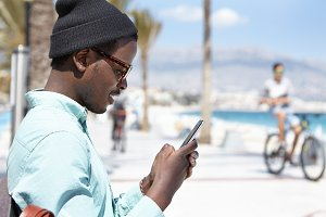 Profile picture of attractive young African American man in hat and shades playing video games using online app on smart phone, enjoying free wireless high-speed internet connection on urban beach