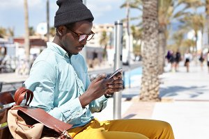 People, technology and communication concept. Fashionable young black man in hat and glasses playing video games online using free city wi-fi on cell phone, waiting for friend on bench by the sea