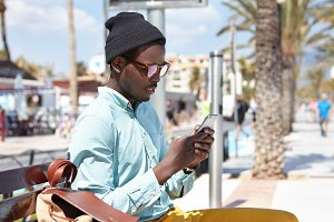 Always in touch. Fashionable black European tourist sitting on bench with backpack using free city wi-fi on mobile phone, looking for cafe or hotel via online map during holidays in resort town