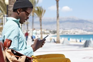 Relaxed carefree African American man wearing hat and glasses messaging online on electronic gadget, looking through newsfeed via social networks, enjoying free wi-fi on promenade by the sea