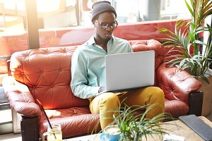 Fashionable young black European freelancer using free wi-fi internet at hotel lobby, working on project remotely, sitting on red leather sofa with laptop computer and drinking coffee during vacations