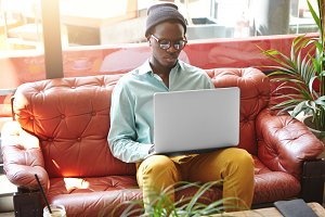 Indoor shot of attractive young African American freelancer wearing stylish clothing and accessories working distantly on notebook computer, sitting on couch in hotel during vacations abroad