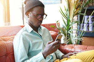 Serious young dark-skinned male in trendy hat and eyewear relaxing on red leather sofa in hotel or restaurant, surfing internet on mobile phone. People, lifestyle, modern technology and communication