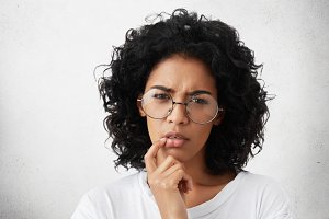 Serious attractive young dark-skinned European woman wearing white casual t-shirt and round glasses keeping finger on her lips, having thoughtful indecisive look, thinking about something important