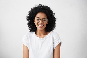 Portrait of charismatic and charming young African woman with curly hair wearing sylish spectacles, smiling widely, narrowing her eyes in expectation of surprise from her boyfriend, looking happy