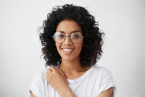 Mixed race black college girl with curly hairstyle smiling broadly at camera dressed in white blouse, looking fresh and young, wearing fashionable eyeglasses. Positive human emotions and feelings